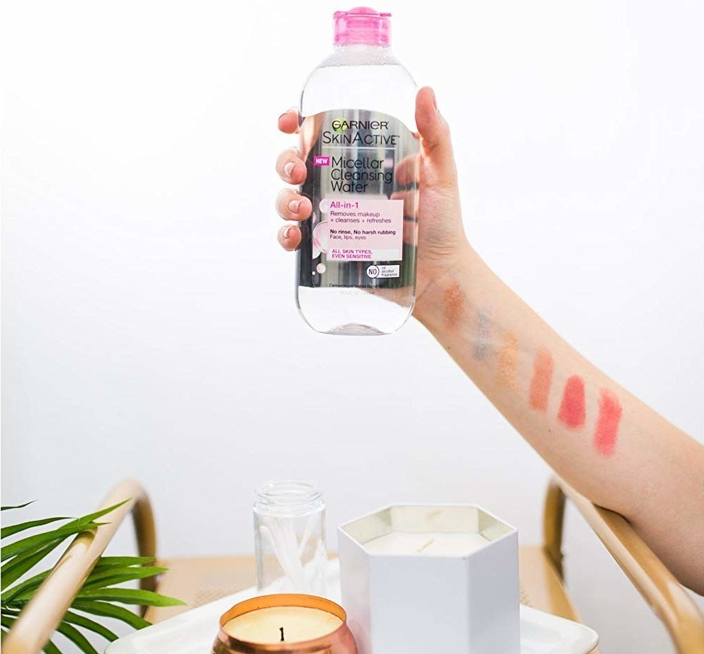 A hand holding the bottle of micellar water