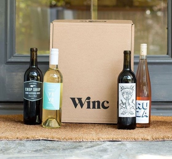 "a ""winc"" box on a doorstep with two bottles of red wine, one bottle of rosé, and one bottle of white wine"