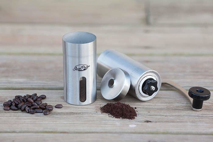 manual coffee grinder with a handle sits on a wood table separated into three parts and showing both whole and ground coffee beans