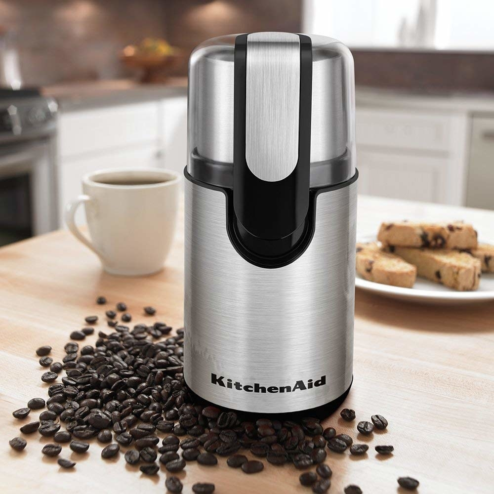 stainless steel KitchenAid grinder surrounded by coffee beans