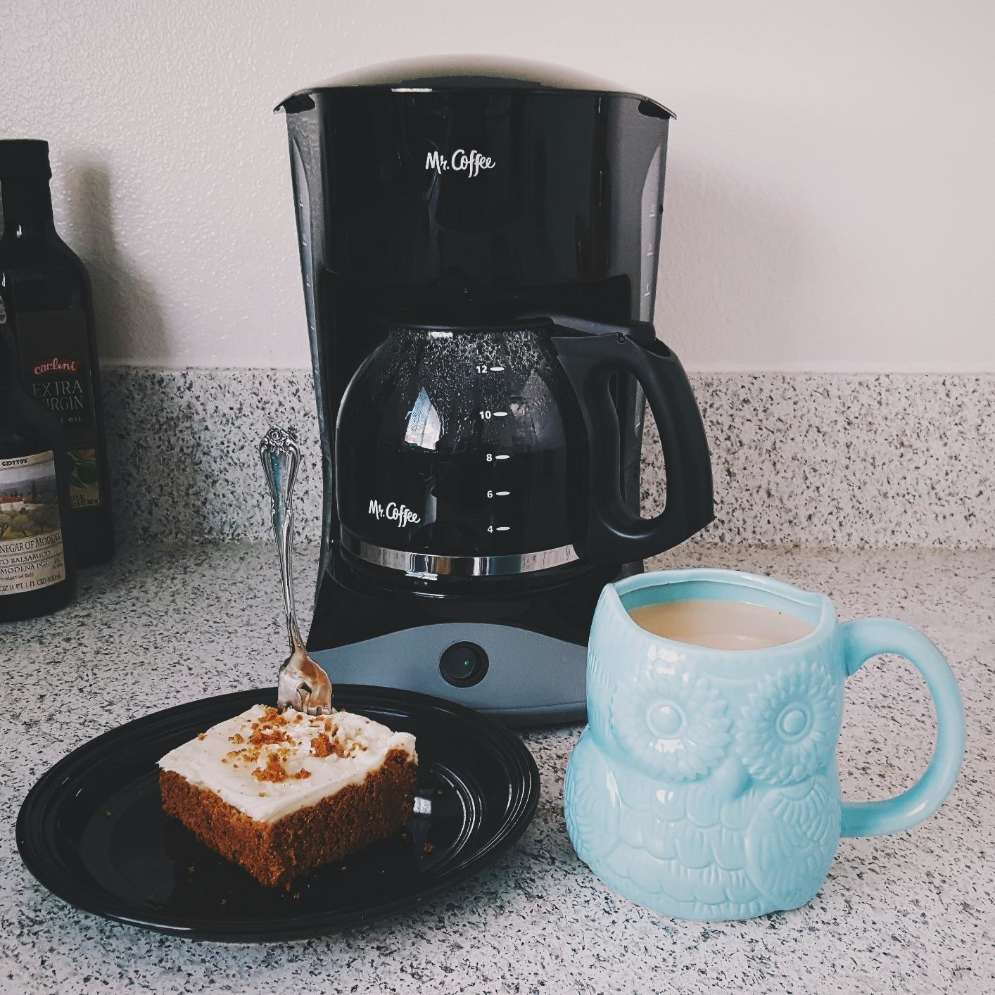 black Mr.Coffee pot full of coffee on a counter next to some coffee cake and a blue owl mug