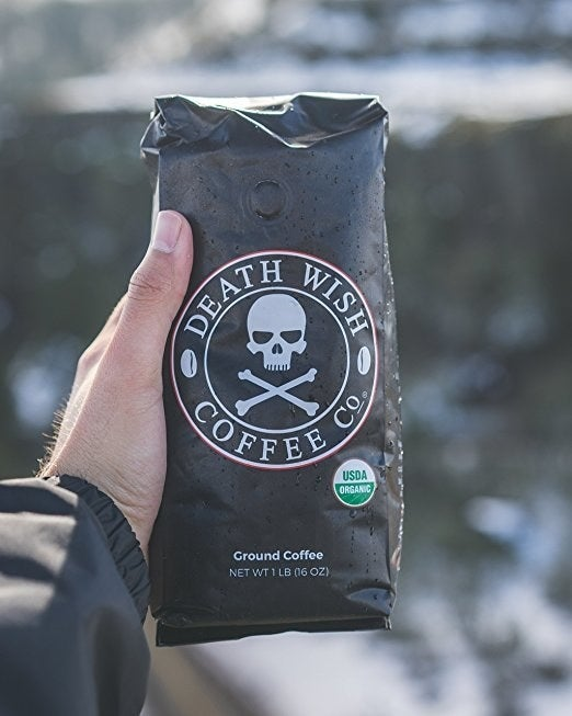 "black bag of death wish coffee printed with a skull and crossbones in someone's hand. reads ""Death Wish Coffee Co., USDA organic, Ground Coffee, 1lb"""