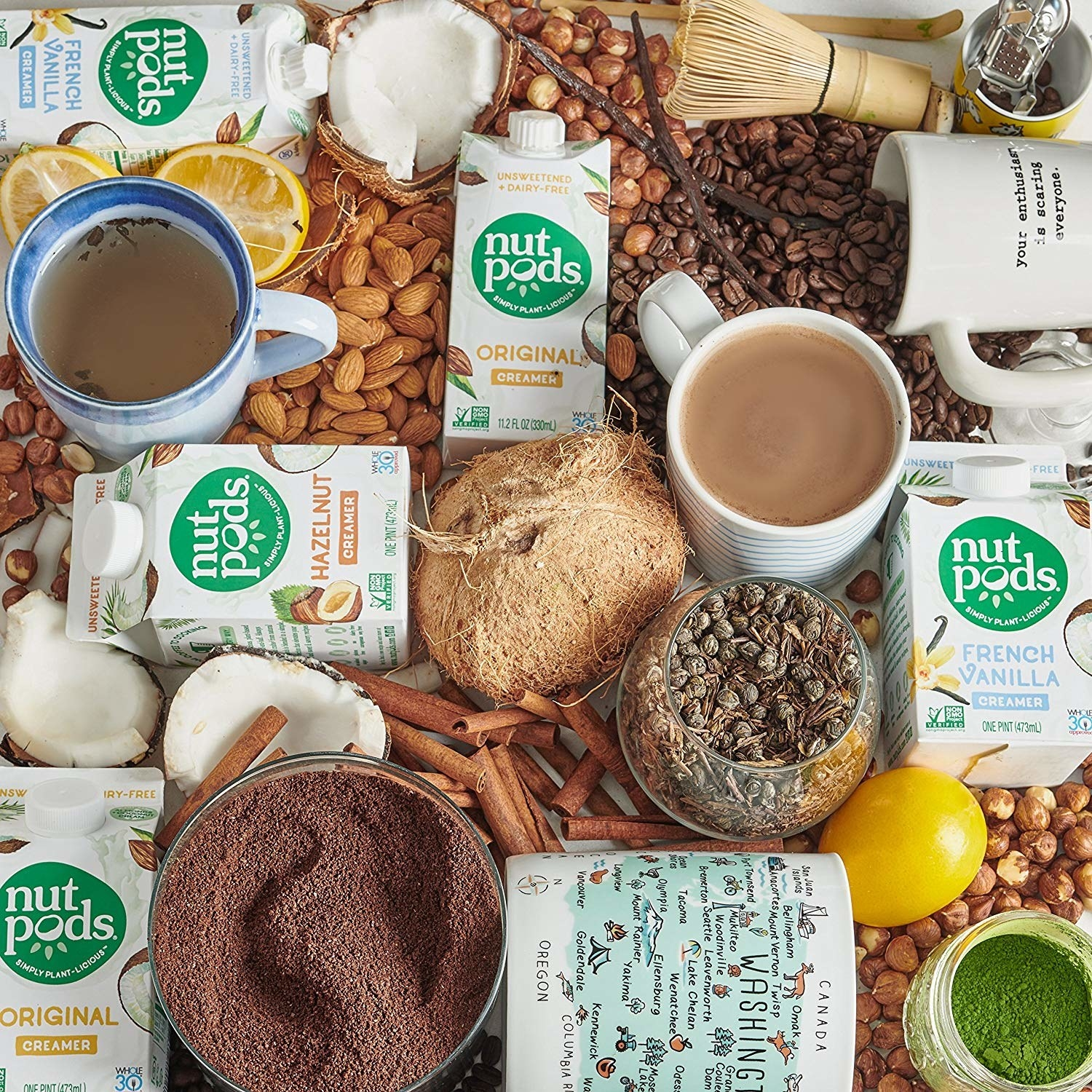 nutpods creamer containers in a flatlay with coconuts, cinnamon, lemons, and various nuts,
