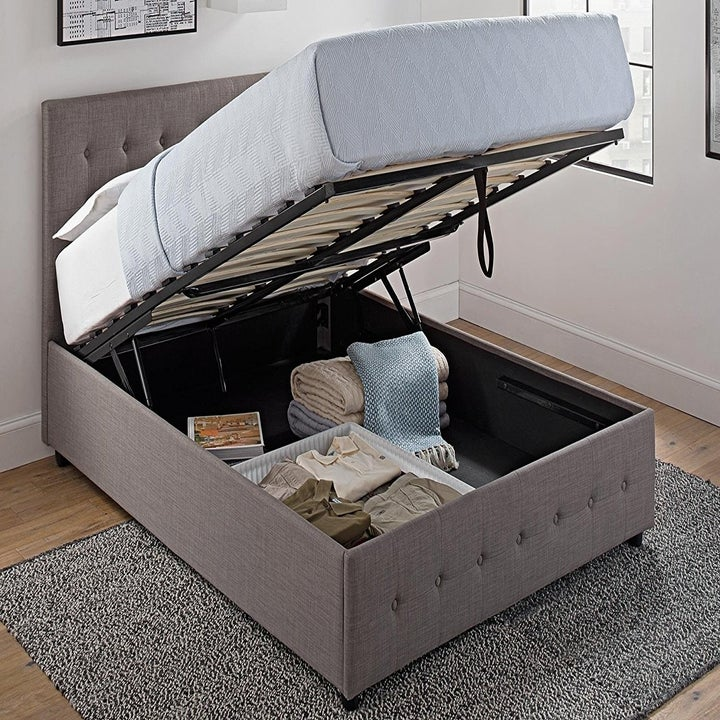 the same bed with the frame lifted up to reveal the storage area underneath