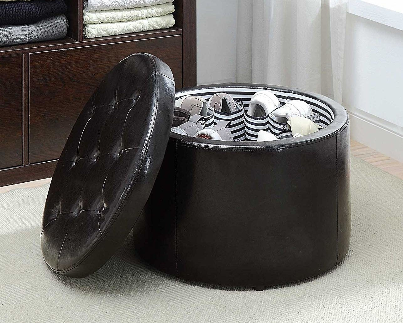 A round black ottoman with a tufted lid, showing that there are pockets on the inside that hold shoes
