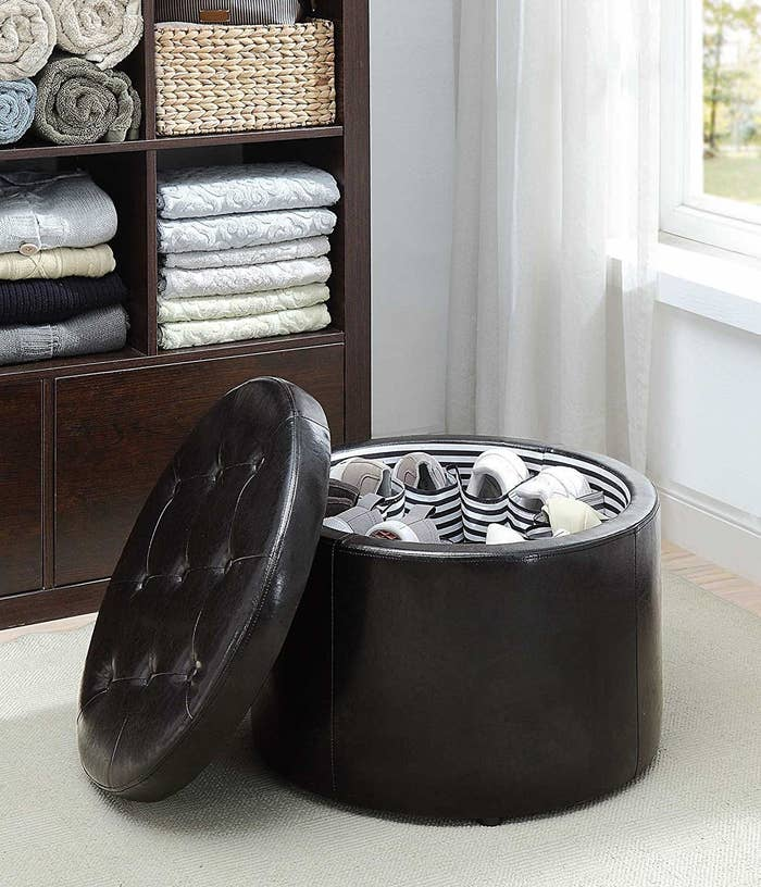 the round ottoman with a tufted lid next to it, showing the inside with spaces to hold pairs of shoes