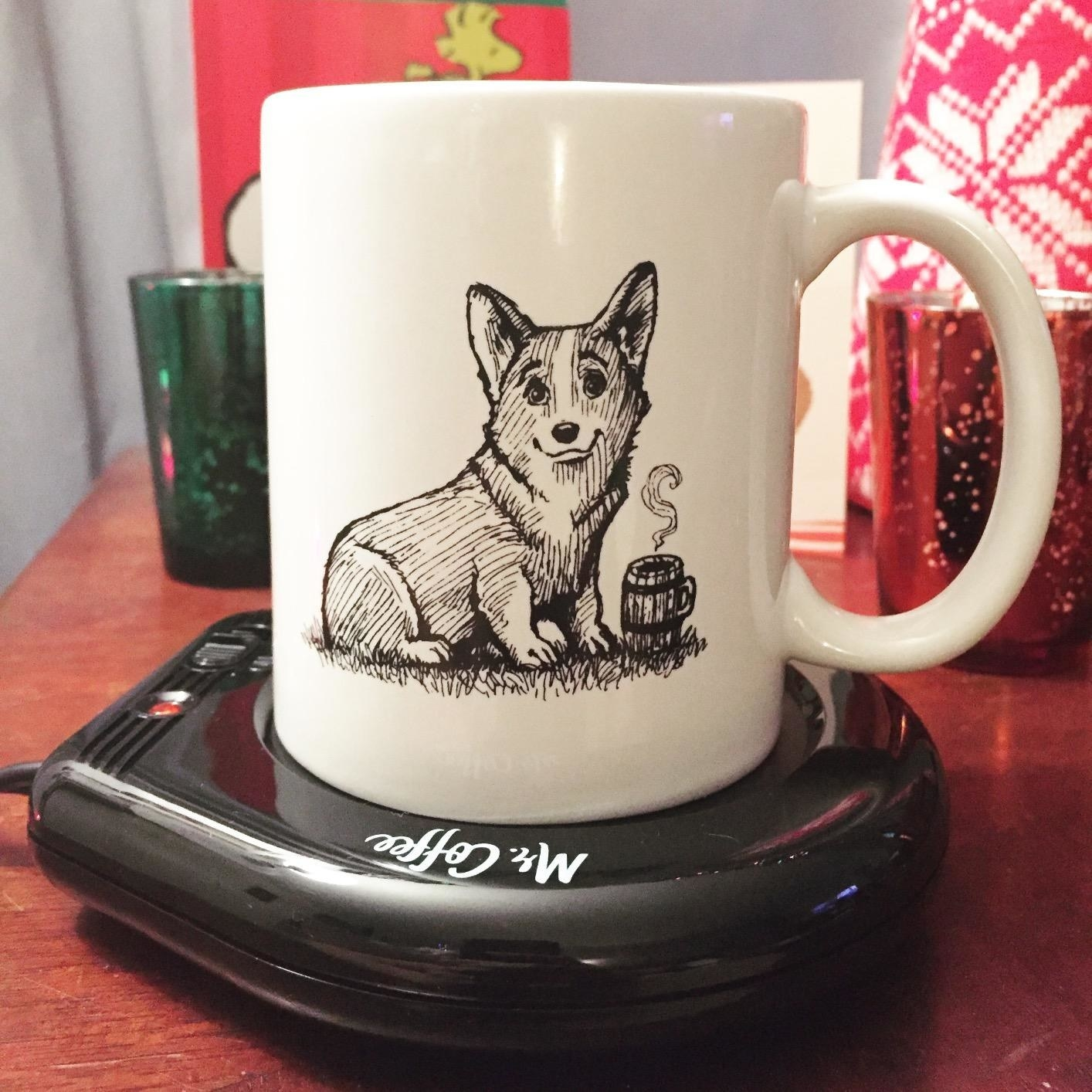 a mug with a drawing of a corgi with a coffee mug on it sitting on a flat black Mr. Coffee mug warmer