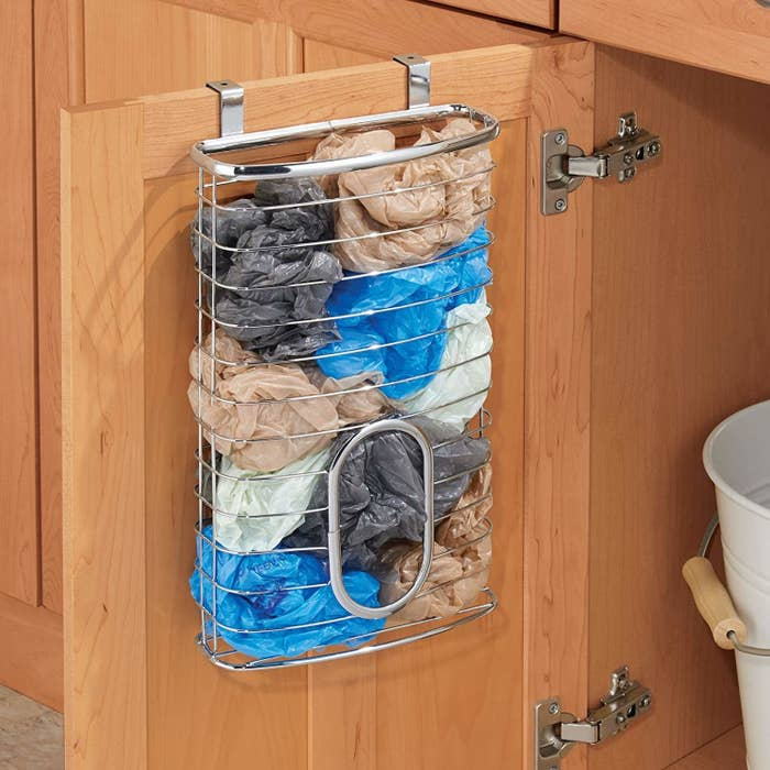 "Promising review: ""This is a great product, I really love it! Exactly what I was looking for and needed to keep my bags in a much nicer way and more accessible to us. We used to store extra bags in a bag hanging on the handle of the door — that always irritated me. So when I saw this way to store my bags, I was very excited. The product is a nice heavyweight wire that does not look cheap and doesn't move while hanging on the cabinet door due to the foam backing on the hangers."" —Fur Kid MomPrice: $13.99 (available in eight finishes)"