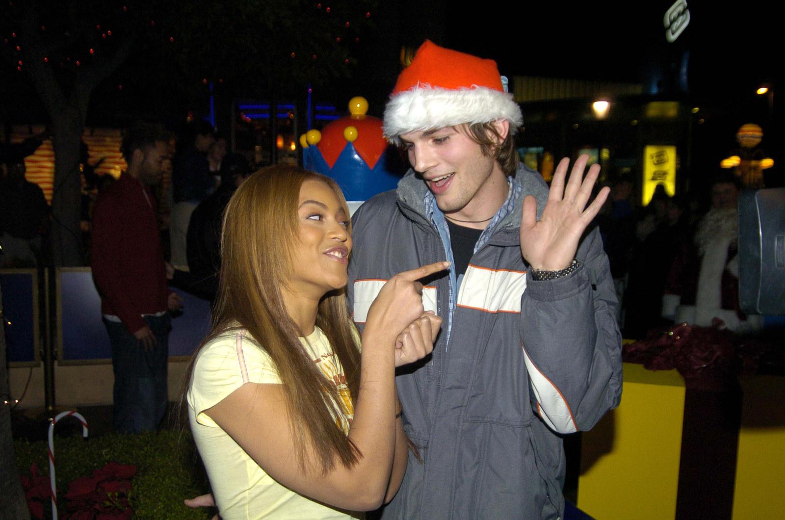 Pointing at Ashton Kutcher's hand.