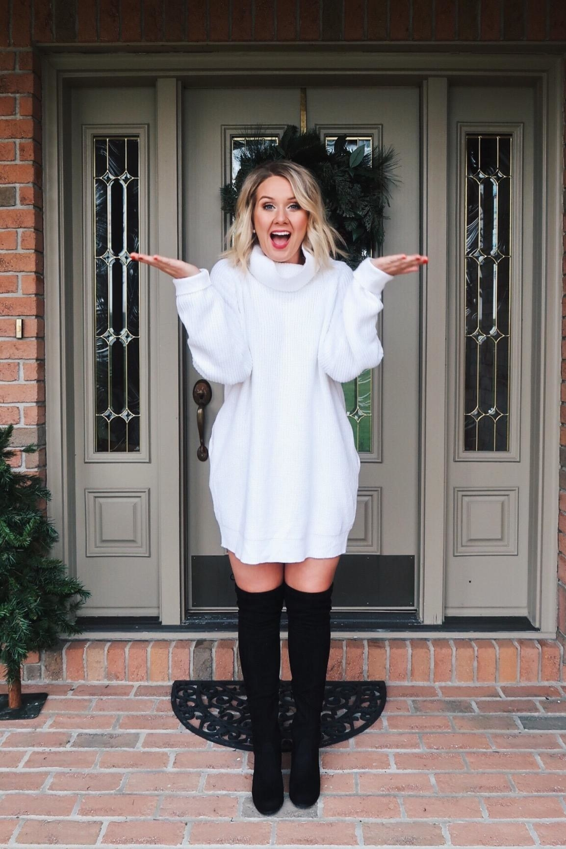 a reviewer wearing the sweater dress in white with black knee-high boots