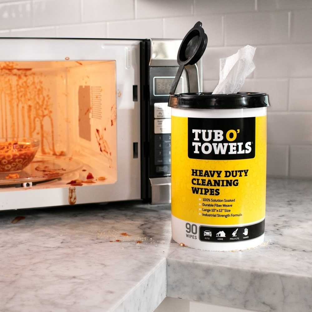 a tub of heavy duty cleaning wipes next to a dirty microwave