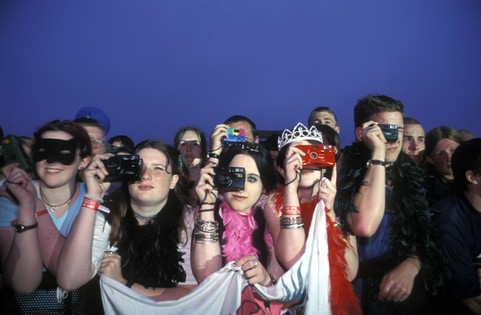 a row of people taking pictures on their cameras
