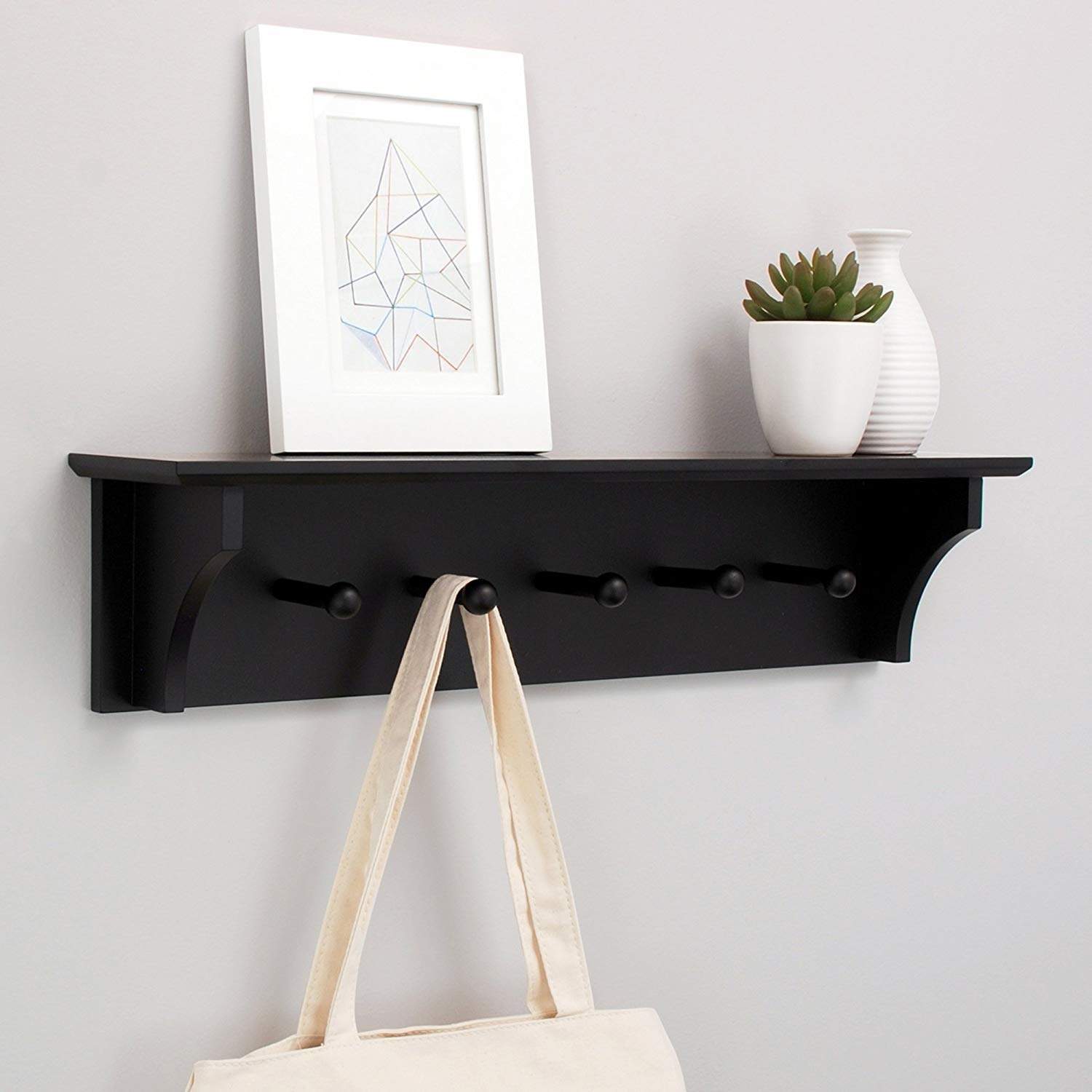 "Promising review: ""I moved in with my boyfriend only to find his storage solution for dog leashes was a pile on the floor. I bought this, and hung it up and it holds all of the dog leashes and my bags now and looks great! We have a couple of picture frames sitting on the shelf part. It's very sturdy."" —FrankieGet it from Amazon for $29.99 (available in black and white)."