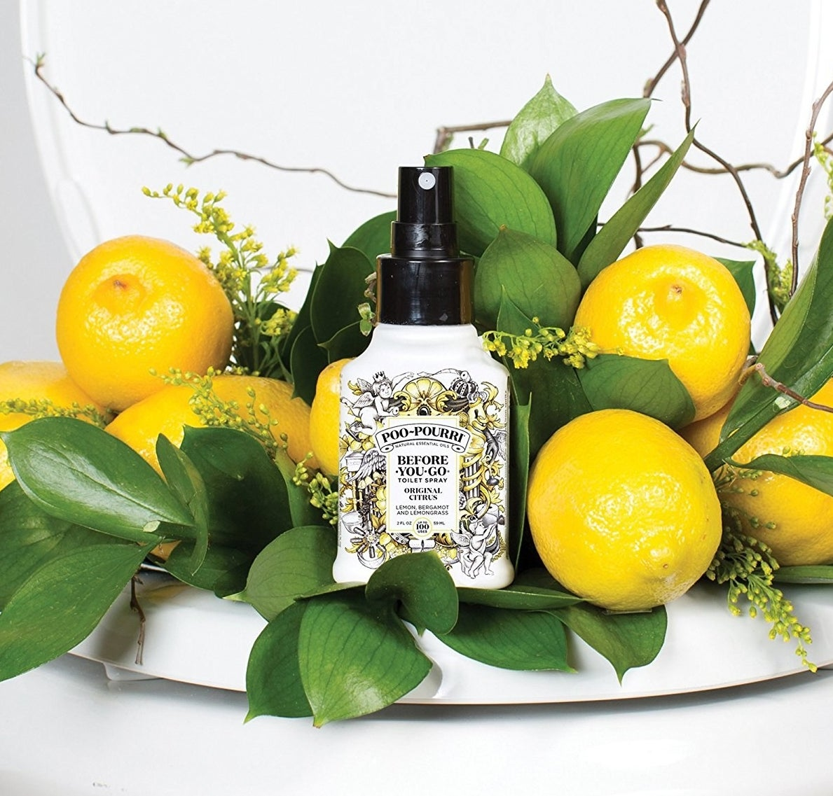 the bottle of poo-pourri displayed next to some lemons