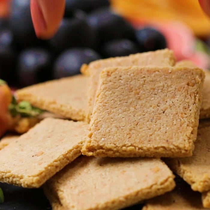Servings: 4 INGREDIENTS2 cups almond flour1 teaspoon salt½ teaspoon pepper1 teaspoon garlic powder¼ cup grated Parmesan cheese2 tablespoons avocado oil or olive oil3-5 tablespoons ice waterPREPARATION1.Preheat the oven to 350˚F (180˚C).2.Combine the almond flour, salt, pepper, garlic powder, and Parmesan in a large bowl. 3.Add the avocado oil and mix thoroughly with a fork. 4.Add the ice water, 1 tablespoon at a time, and mix thoroughly, until small clumps form and the dough holds together when squeezed.5.Form the dough into a round, flattening the top and bottom as evenly as possible. 6.Place the dough on a sheet of parchment paper and add another piece of parchment on top. Roll out the dough as evenly as possible, to between ¼- and ⅛-inch thick.7.Remove the top layer of parchment paper and place on a baking sheet. You may need to press the edges of the dough to form an even rectangle.8.Using a cookie cutter or pizza cutter, slice the dough to desired size. If using a cookie cutter, re-roll the excess dough and cut out more crackers. If desired, use the blunt end of a skewer to poke holes in each of the crackers. 9.Carefully place the crackers on the baking sheet. If the dough is too warm, the crackers will break as you attempt to transfer them. Chill in the freezer for 10 minutes before proceeding if this happens.10.Bake for 15-20 minutes, flipping halfway, until golden brown. 11.Let the crackers cool completely and serve as desired. Store up to 1 week at room temperature in an airtight container. 12.Enjoy!