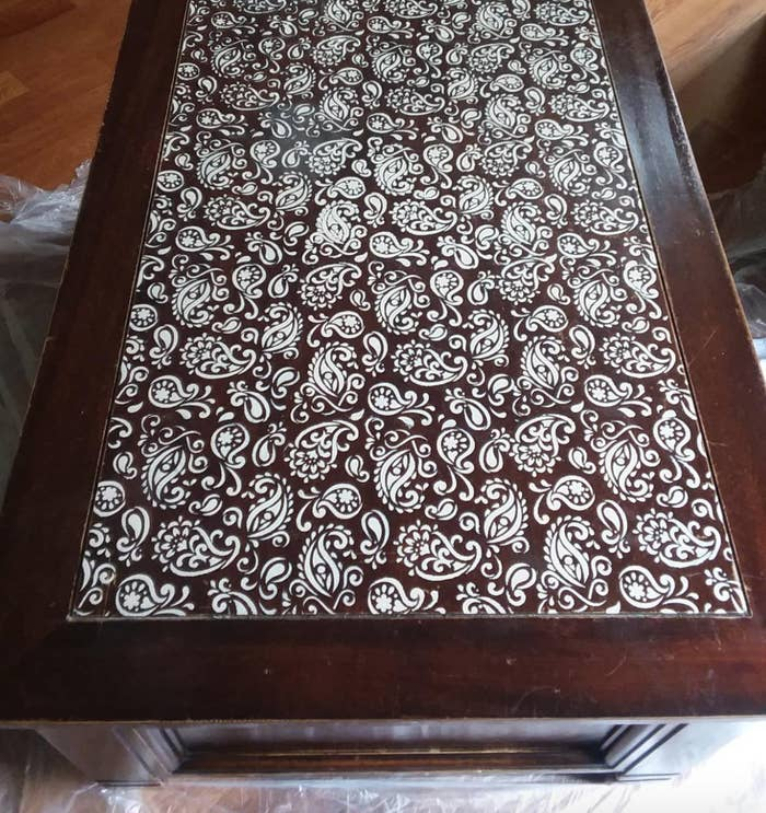 A wood coffee table with the stenciled white paisley pattern on top