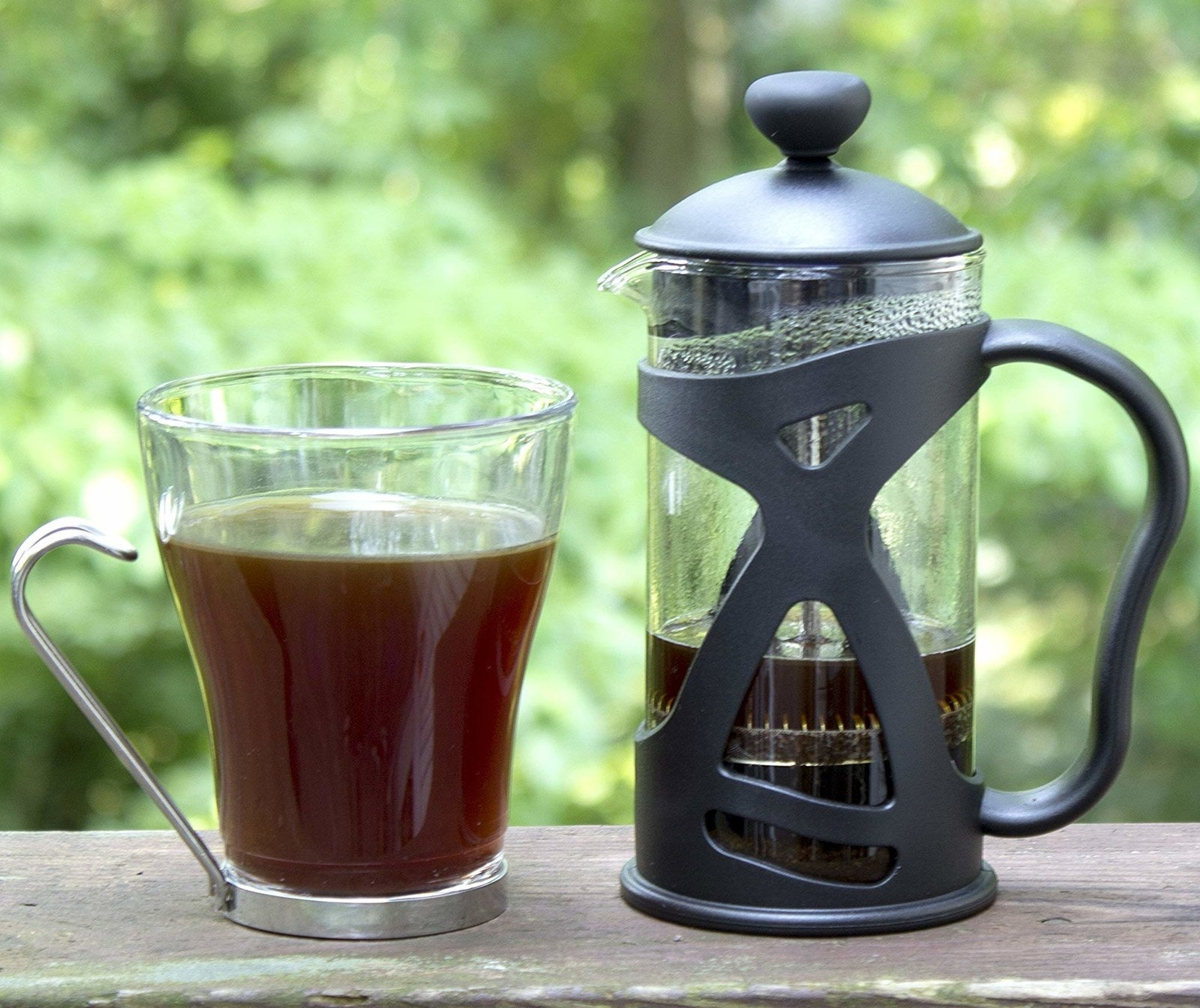 used black french press next to a clear mug of black coffee