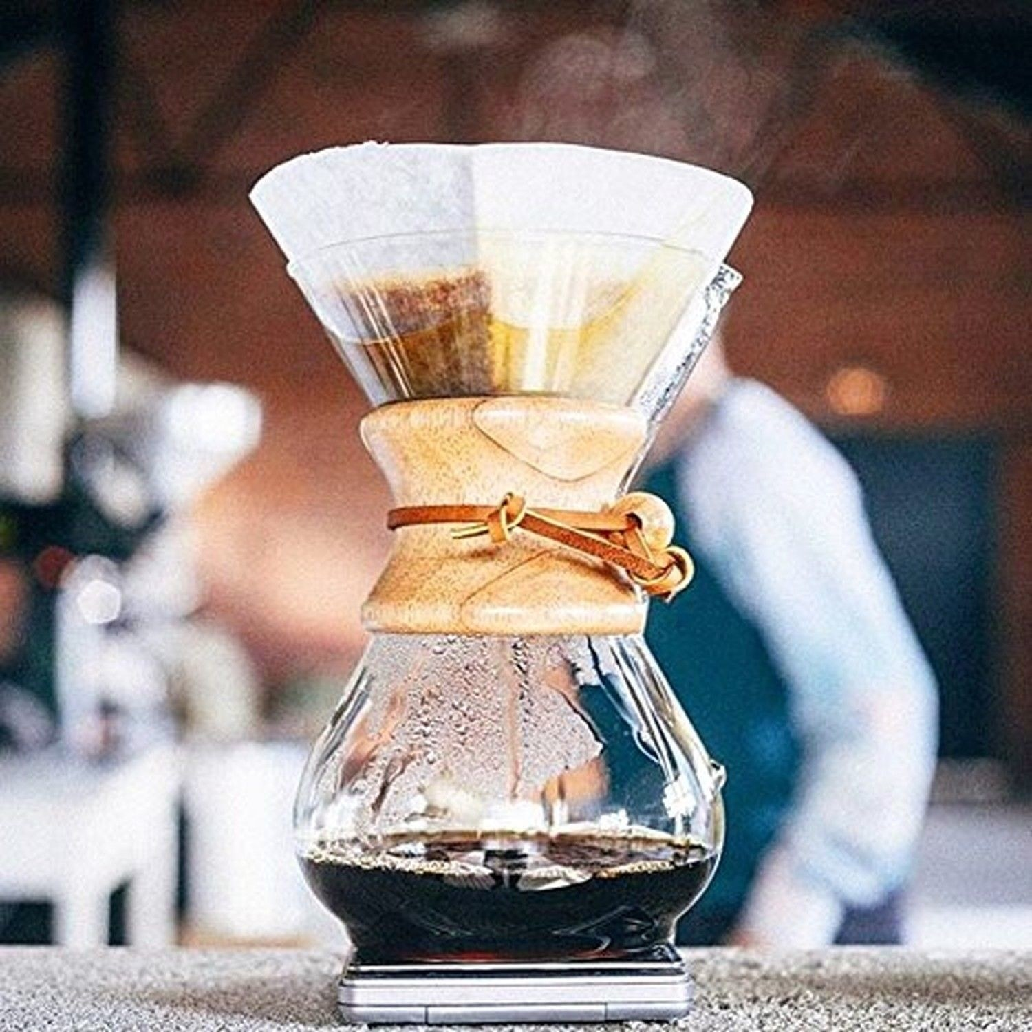 glass chemex shaped like an hour glass with coffee in the bottom vessel