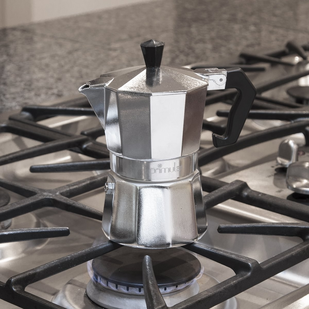 a metal stovetop espresso maker over a gas stove