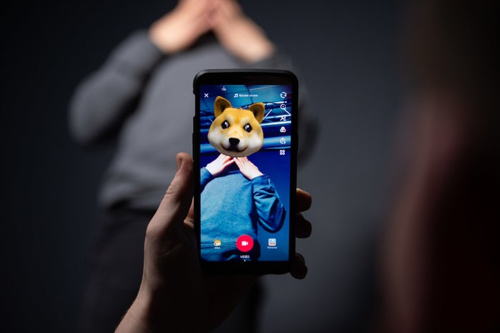 Someone poses for a picture using TikTok.