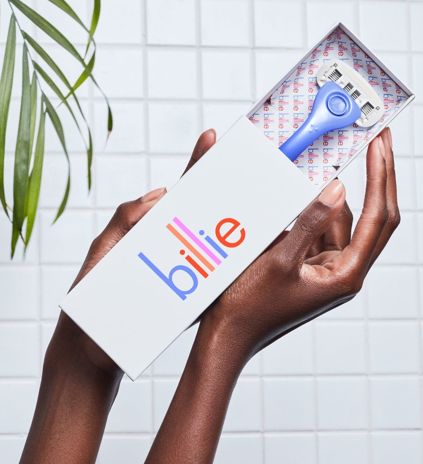 "Hands holding a ""Billie"" box with a periwinkle razor peeking out"