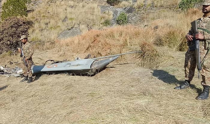 Pakistani soldiers stand next to what Pakistan says is the wreckage of an Indian fighter jet shot down in Pakistan-controlled Kashmir on Feb. 28.
