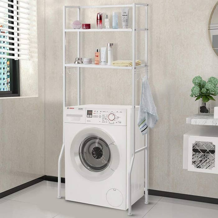 white metal rack over a washing machine with two shelves and three hooks on either side