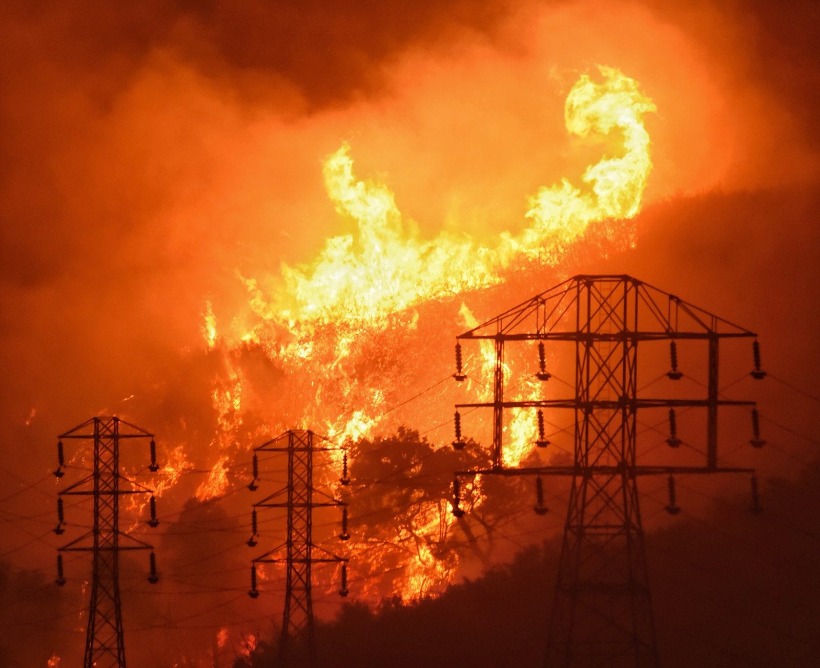 FILE - In this Dec. 16, 2017, file photo provided by the Santa Barbara County Fire Department, flames burn near power lines in Sycamore Canyon near West Mountain Drive in Montecito, Calif. State fire officials blamed power lines coming into contact with trees for sparking four Northern California wildfires last October that incinerated more than 130 buildings.