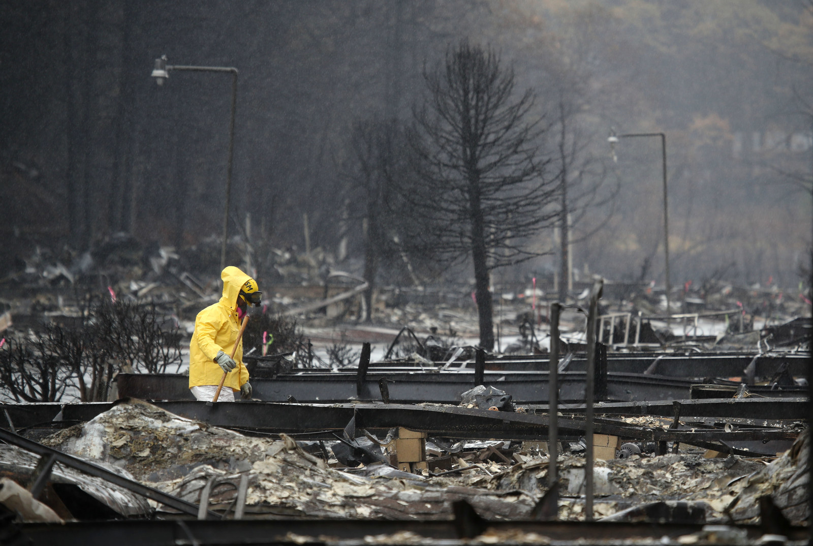 A search and rescue crew member searches for human remains at a mobile home park destroyed by the Camp fire in Paradise, California.