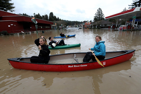 Sierra Steele and Rachael Parent paddle through the center of Guerneville.