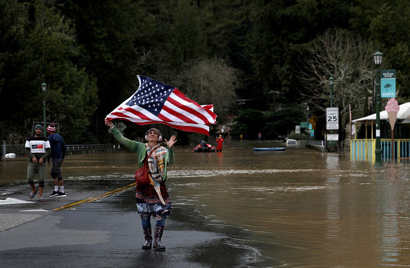 Malina Pettibone, a Guerneville native, dances with an American flag while listening to Nelly Furtado as the Russian River waters rise.
