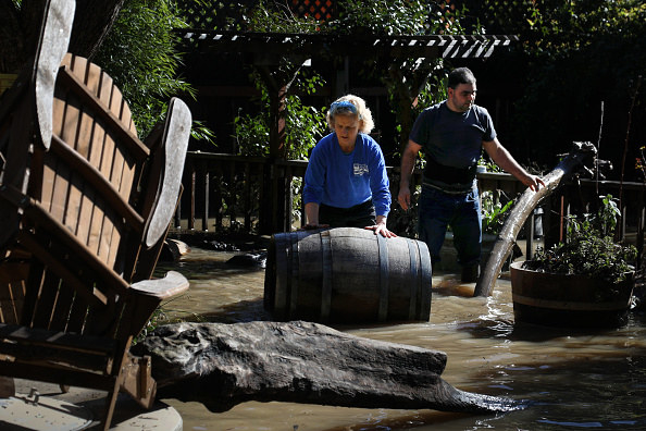 Jude Lamarre and Mario Barajas clean up the flooded patio area of the Ferngrove Cottages in Guerneville.