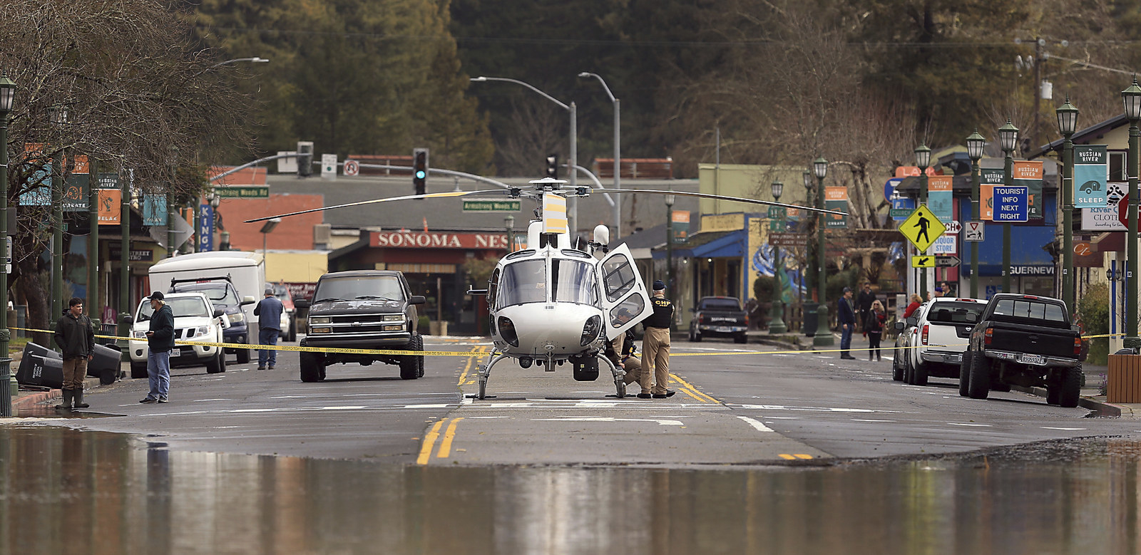 A police helicopter uses Main Street in Guerneville, Calif. as a landing pad as water continues to rise.