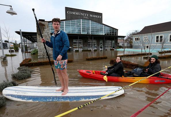 Gabe Ghirann, left, Taylor Weber, middle, and Nicco Weisskoff paddle through flood waters from the Laguna de Santa Rosa near The Barlow market in Sebastopol, Calif.