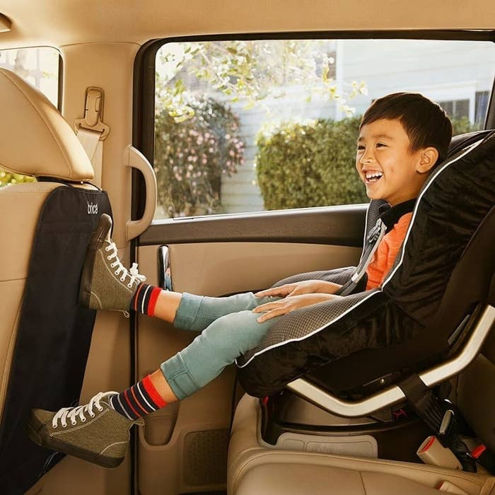 A kid in a backseat of a car with their feet kicking the front seat but the cover is protecting the back of the car seat
