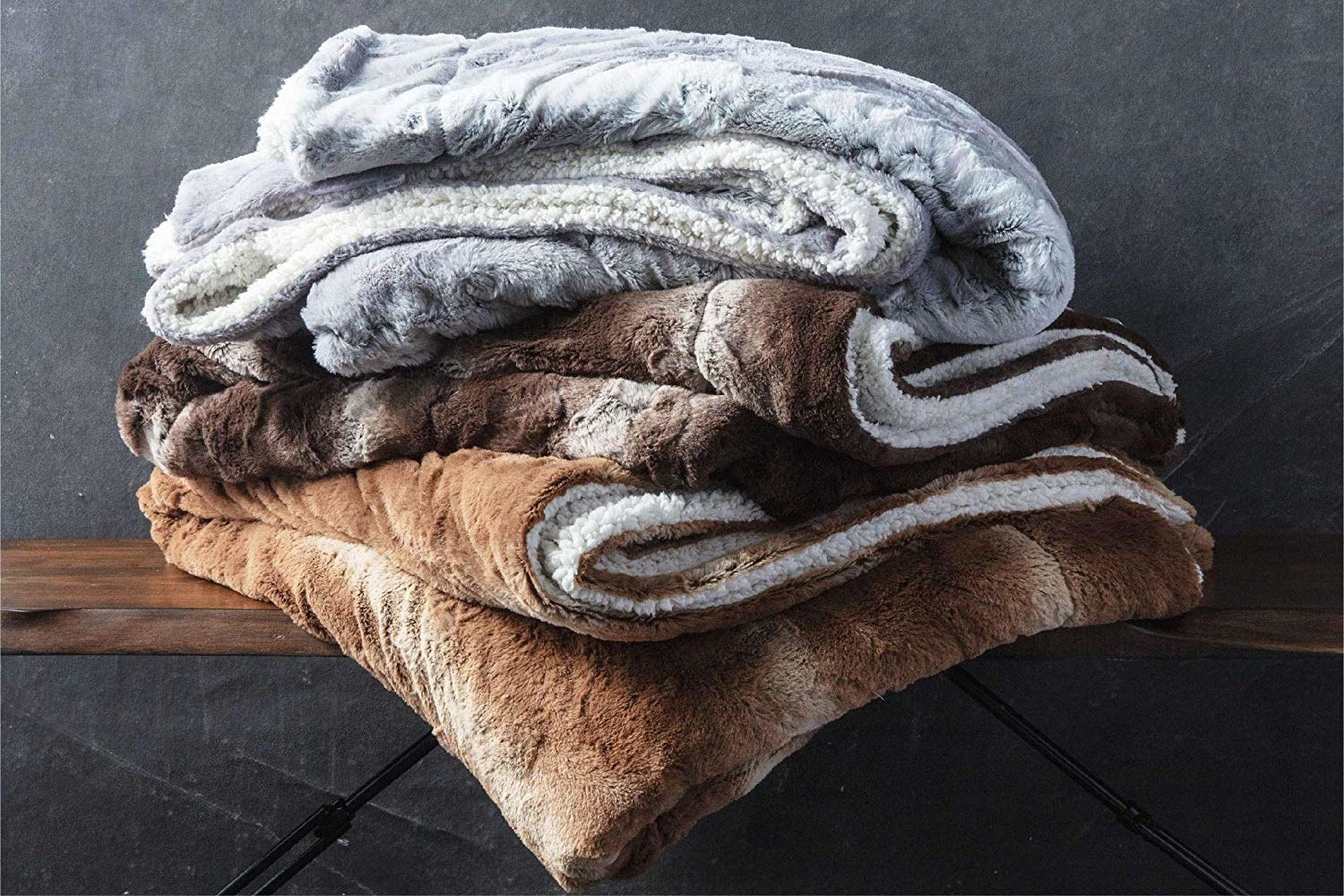 throws in light brown, dark brown, and grey, each with a faux-sherpa reverse side