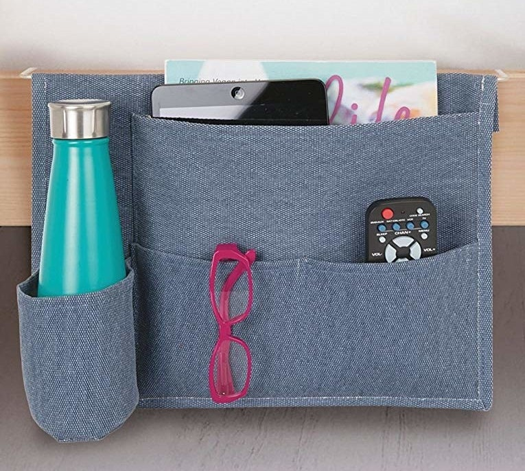 """Promising review: """"My nightstand was getting too cluttered and I couldn't stand it. This is a great solution! It fits two remotes, my glasses, a tablet stand, and my Kindle Paperwhite. The bottle holder is a great bonus. It seems pretty stuck between the mattress and box spring, so it won't move or fall down. Overall, I'm very pleased with this product!"""" —SarahJGet it from Amazon for $11.99 (available in five colors)."""