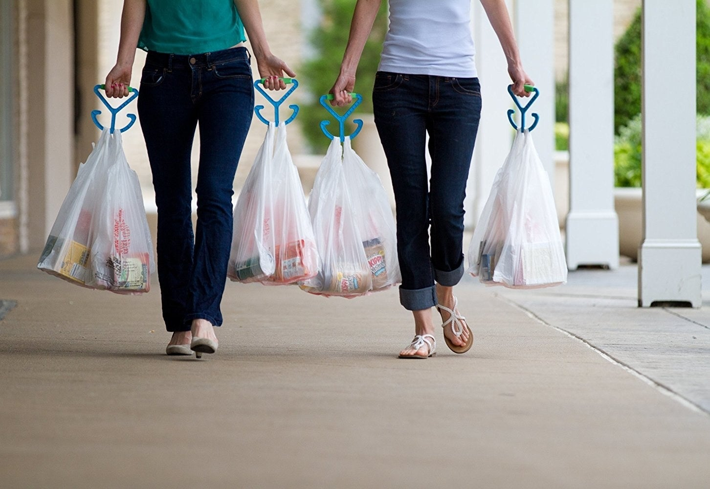 two models using a bag handle in each hand to carry lots of grocery bags