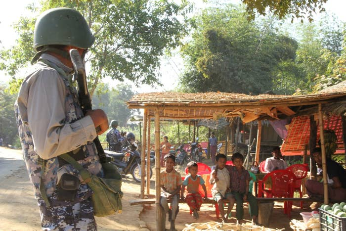 A Myanmar border guard police officer and a group of Rohingya Muslims during a government-organized visit for journalists in Buthidaung townships in Rakhine state on Jan. 25.