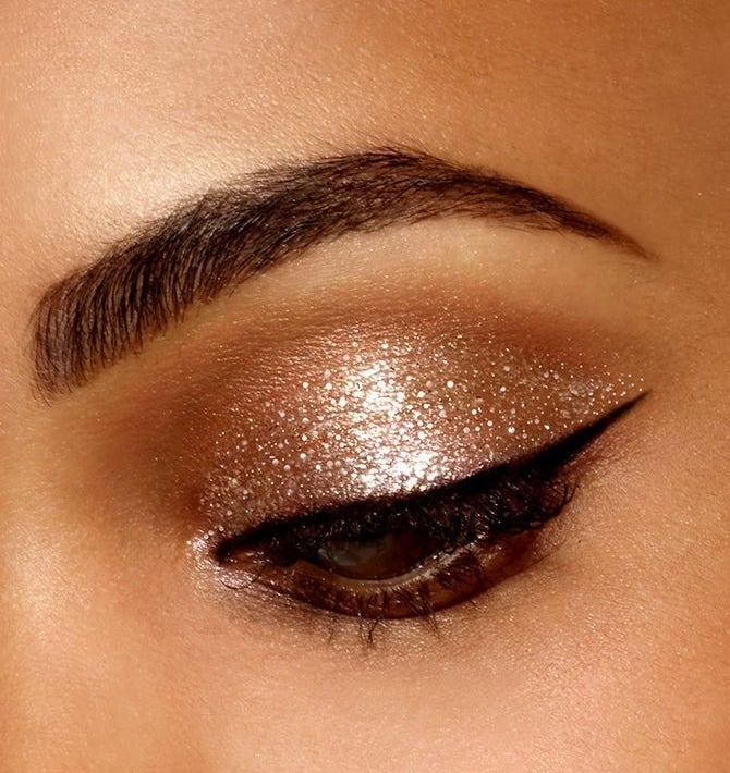 An eye with sparkly gold eyeshadow and sharp cat eye liner