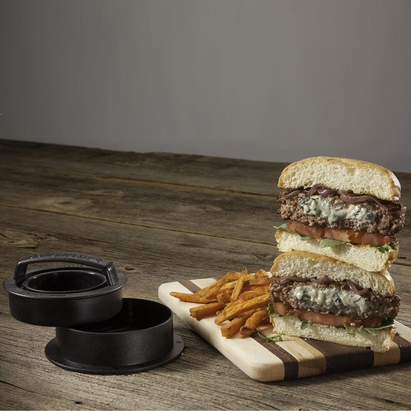 The black burger press top and bottom next to a cutting board with a burger cut in half, stacked on top of each other, to show how it's stuffed with cheese
