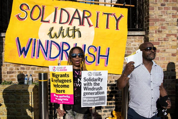 Demonstrators chant and hold placards during a protest in support of the Windrush generation in Windrush Square, Brixton, on April 20, 2018 in London.