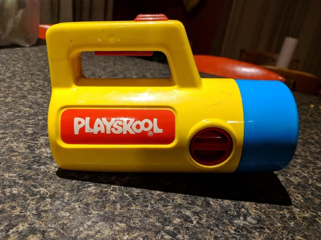 Close up shot of a yellow and blue Playskool flashlight