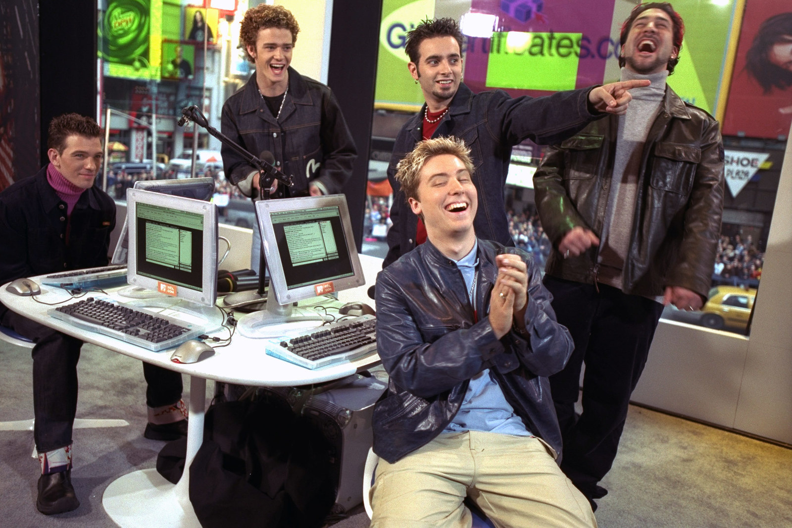 N' SYNC laughing while surrounding desktop computers.