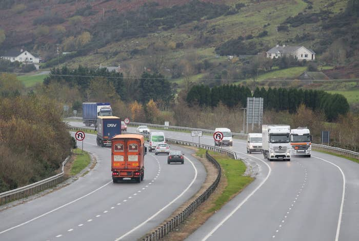 Traffic crosses the border, marked by the no U-turn sign, between Northern Ireland and Ireland outside Newry.