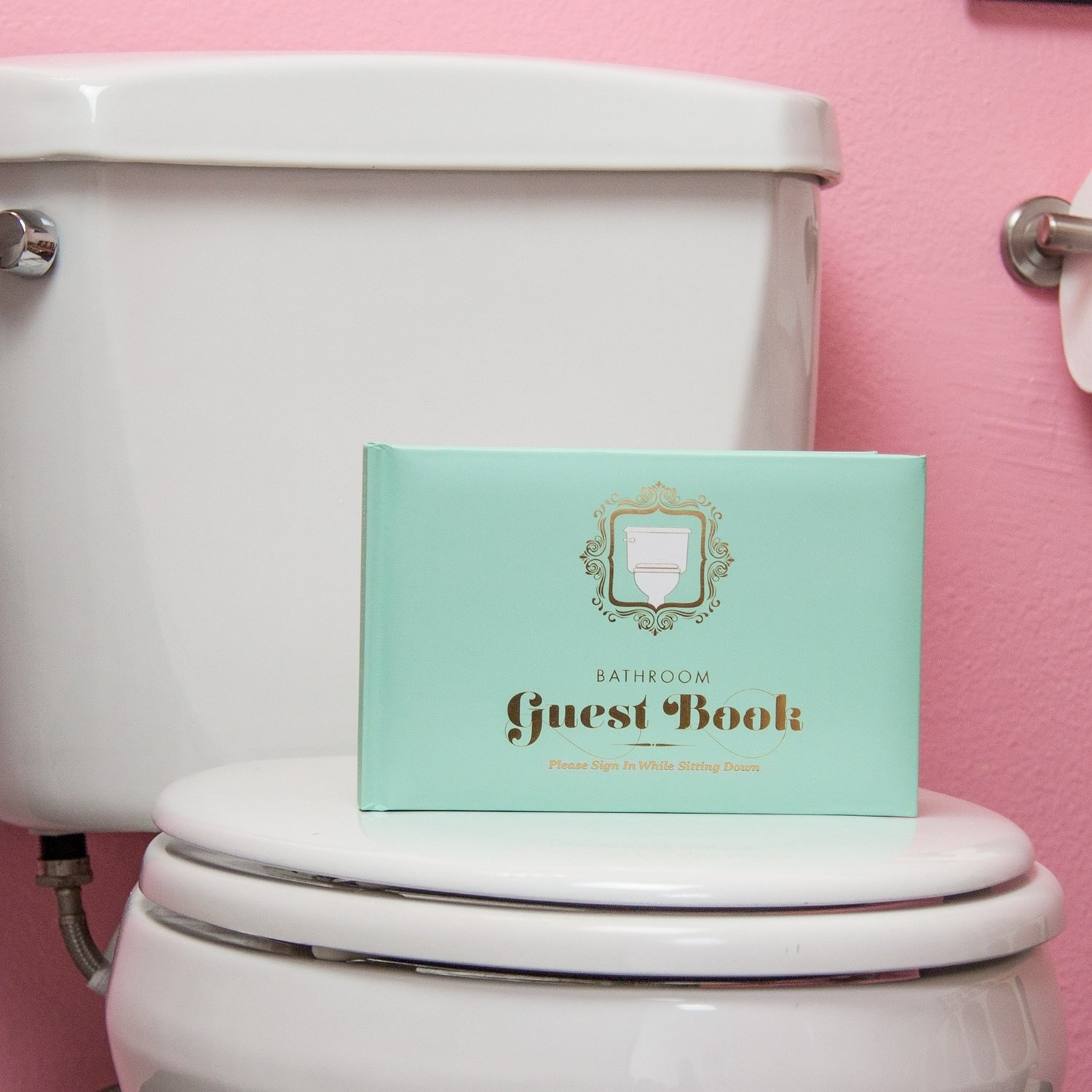 guest book with a fancy cover on a closed lid of a toilet