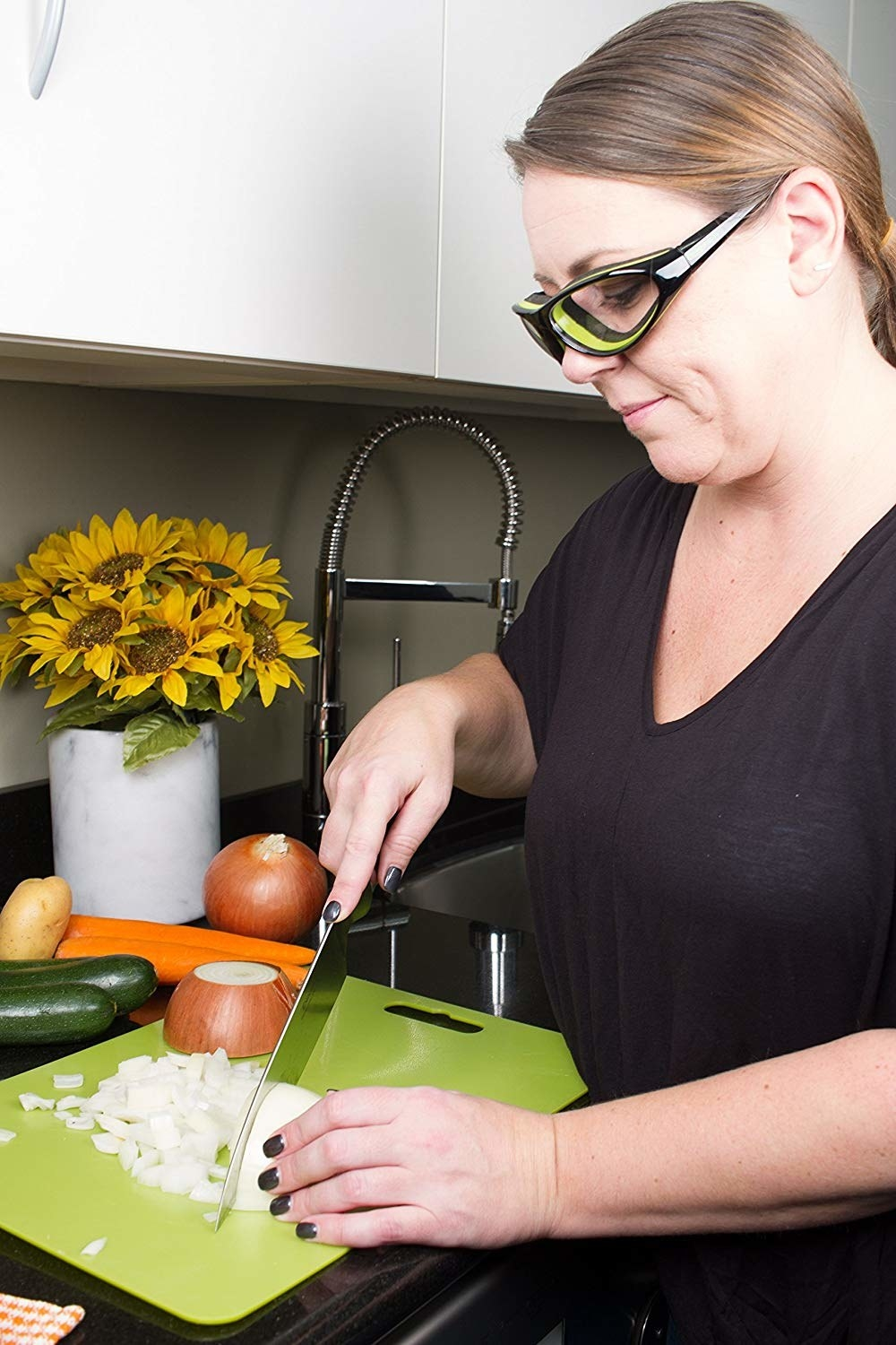 Model wearing the glasses and chopping a white onion