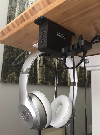 a reviewer using the under desk organizer to hang their head phones