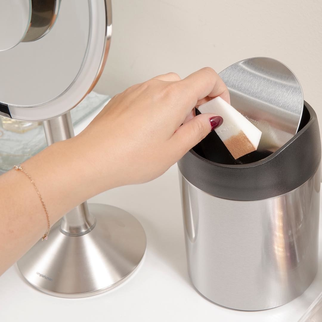 hand putting makeup sponge in stainless steel countertop garbage can