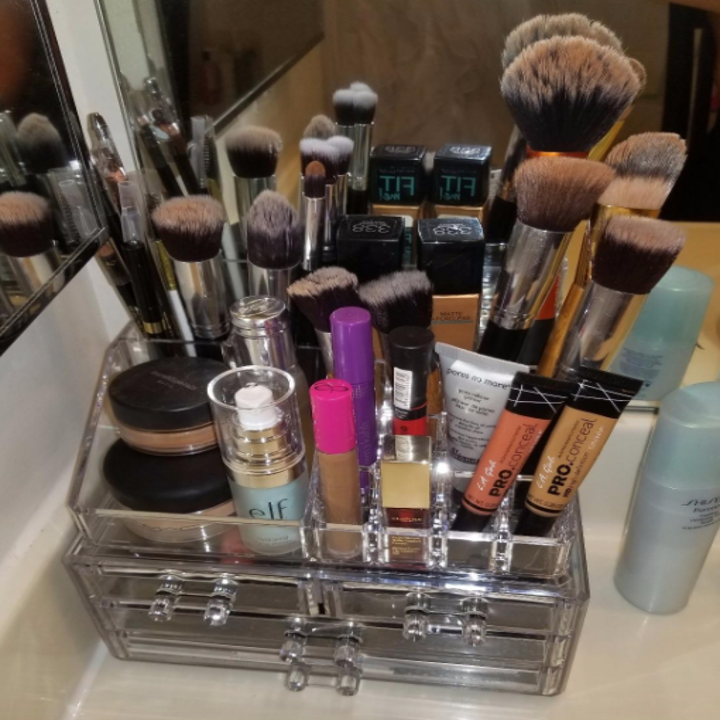 A reviewer's makeup and brushes clearly stored in the organizer